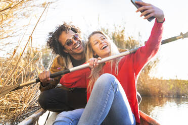 Happy couple taking selfie with oar through mobile phone while sitting in canoe on river - SBOF02693