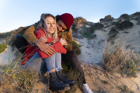 Affectionate couple smiling while sitting on sand dune during sunset - SBOF02699