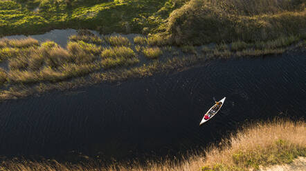 Young couple canoeing on river by grass area during sunset - SBOF02702