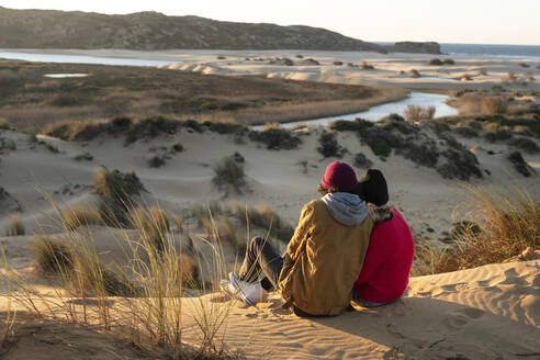 Couple wearing knit hat sitting together on sand dune during sunset - SBOF02711