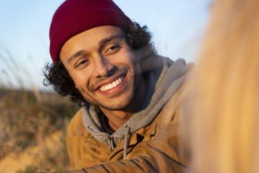 Man wearing knit hat smiling while looking at woman outdoors - SBOF02717