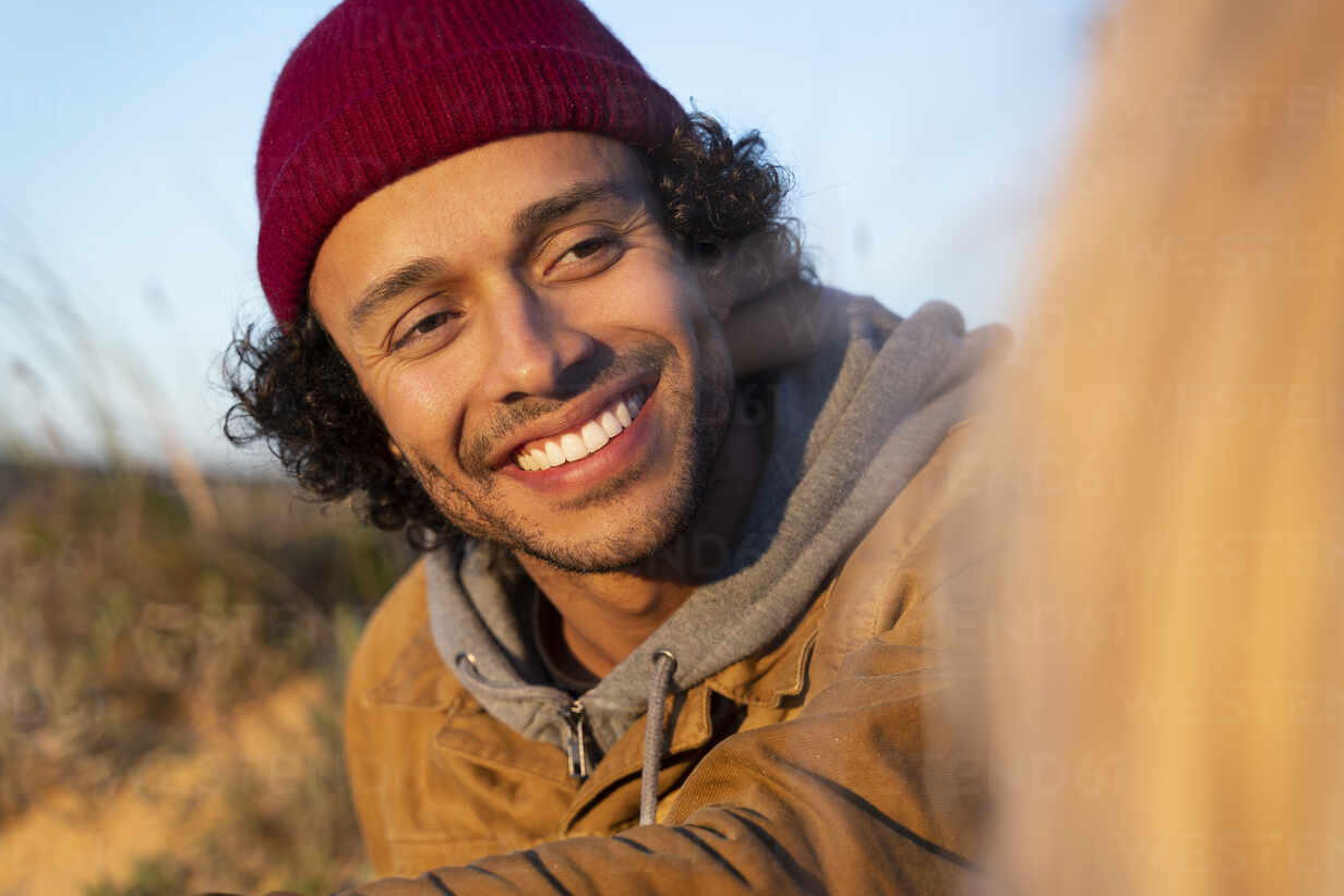 Portrait of smiling young man sitting in the dunes at sunset looking at his girlfriend - SBOF02717 - Steve Brookland/Westend61