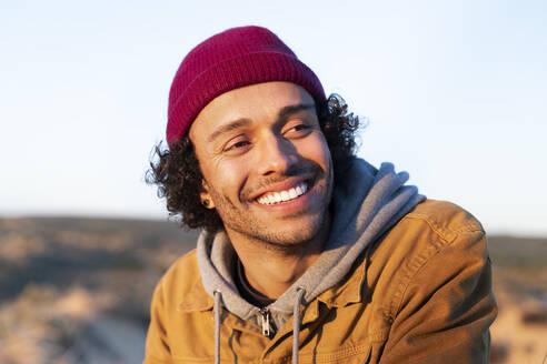Smiling man wearing knit hat looking away while sitting outdoors - SBOF02720