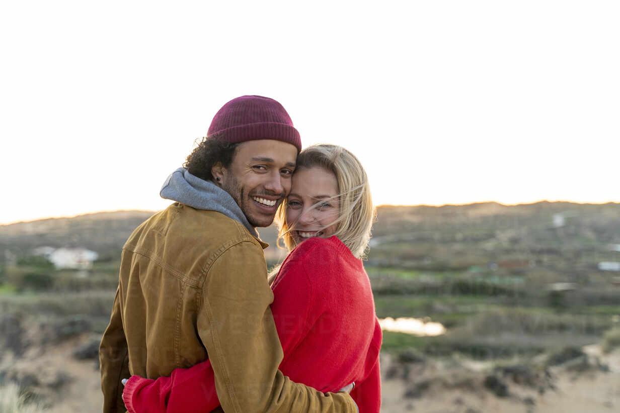 Lächelndes junges Paar schaut über die Schulter, während es mit dem Arm gegen den Himmel steht - SBOF02726 - Steve Brookland/Westend61
