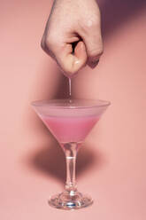 Male hand dipping into cocktail glass with pink dense liquid. Conceptual, sexual life, pleasure, sex, funny, fun, random - AFVF08219