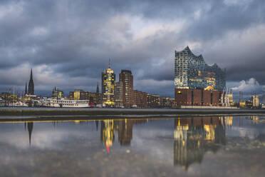 Deutschland, Hamburg, Anleger Theater im Hafen. Hamburger Skyline mit der Elbphilharmonie spiegelt sich in einer Pfütze - KEBF01813