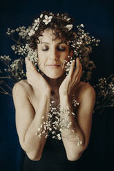 curly hair woman portrait with flowers showing sensity and feminity - GMLF00987