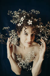curly hair woman portrait with flowers showing sensity and feminity - GMLF00990