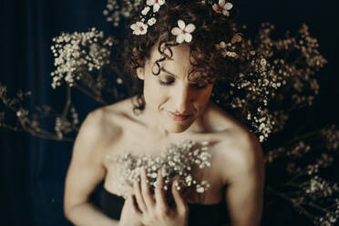 curly hair woman portrait with flowers showing sensity and feminity - GMLF00993