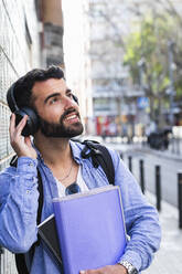 Male entrepreneur with documents looking way while listening music through wireless technology - PNAF00754