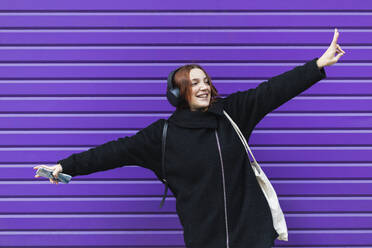 Cheerful young businesswoman dancing against purple shutter while listening music - PNAF00757