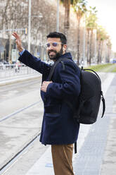 Male professional waving while standing at station - PNAF00760