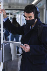Businessman wearing protective face mask using digital tablet while standing in train - PNAF00766
