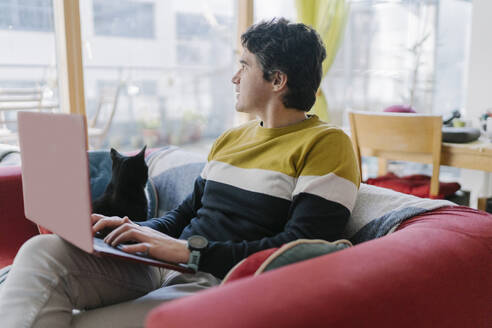Mid adult man using laptop looking away while sitting on sofa at home - BOYF01921