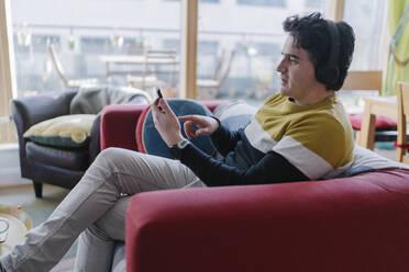 Adult Man listening Music using Bluetooth headphones and a Smartphone - BOYF01924