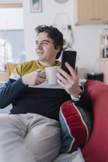 Man with smart phone and coffee cup sitting on sofa while looking away - BOYF01927