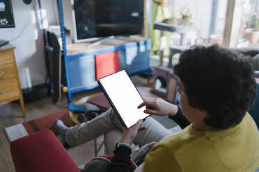 Mid man using digital tablet while sitting on sofa at home - BOYF01930