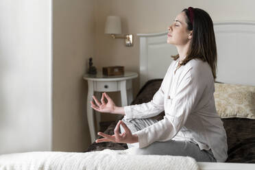 Young woman relaxing on bed in bedroom. Relax, meditation, yoga, stretch, breathing techniques, breath, pranayama, raja yoga, relax, chill, leisure, sunday morning - AFVF08226