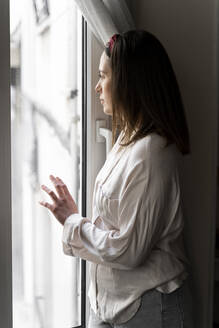 Thoughtful young woman looking though window while standing at home - AFVF08229