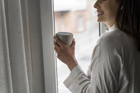 Smiling woman with coffee standing at window - AFVF08232