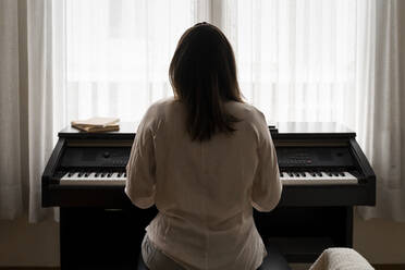 Young woman playing piano at home - AFVF08235