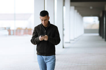 Young boy texting an email with his smartphone while walking at street - OCAF00628