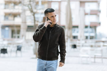 Businessman with blue jeans talking on mobile phone at street - OCAF00634