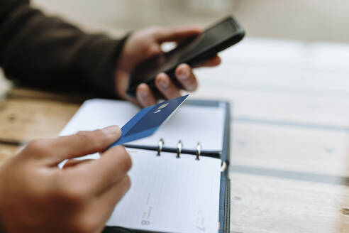 Young man making online payment with credit card through smart phone - OCAF00643