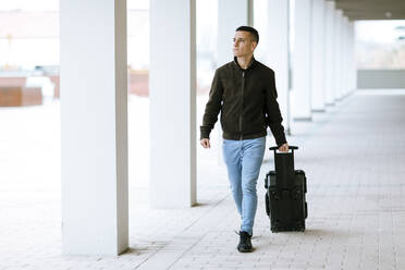 Young boy in blue jeans carrying a suitcase down the street - OCAF00646