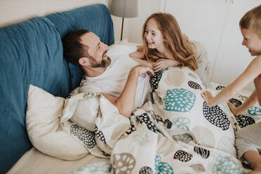 Smiling daughter and son having fun with father on bed at home - GMLF00996