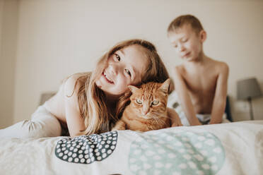 Smiling girl leaning on cat while brother in background in bedroom at home - GMLF00999