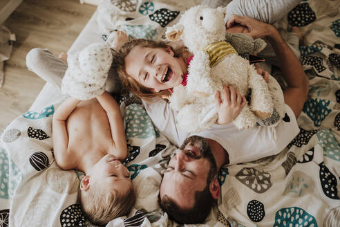 Laughing father and daughter playing while lying on bed with son at home - GMLF01023