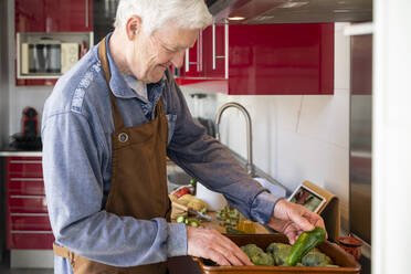 Senior man arranging vegetables while standing in kitchen at home - AFVF08241