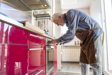 Senior man with apron preparing food in oven at kitchen - AFVF08253