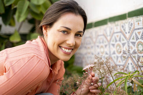 Beautiful smiling woman with blue eyes holding flowers in garden - AFVF08265