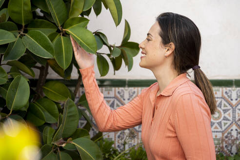 Smiling young woman touching leaves in garden - AFVF08268