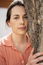 Beautiful woman embracing tree trunk in garden - AFVF08271