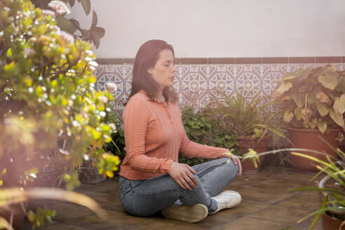 Young woman meditating while sitting on floor at patio in garden - AFVF08277
