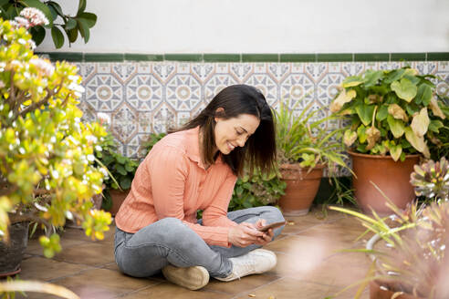 Smiling woman using smart phone while sitting in garden - AFVF08280