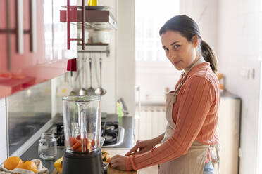 Young woman making healthy fruit smoothie in kitchen. Recipe, videochat, connected, healthy lifestyle, health, fruit, cute, beautiful, stay at home - AFVF08283