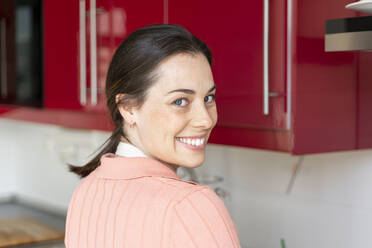 Smiling woman looking over shoulder while standing in kitchen at home - AFVF08286