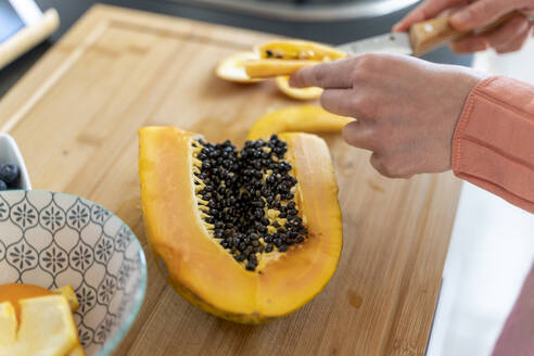 Woman cutting papaya in kitchen at home - AFVF08289
