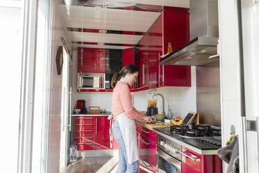 Young woman preparing food while standing in kitchen at home - AFVF08292