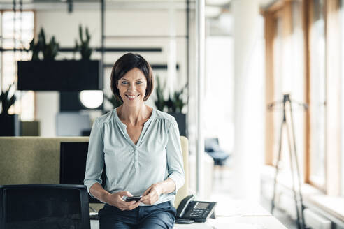 Happy businesswoman with smart phone in office - JOSEF03625