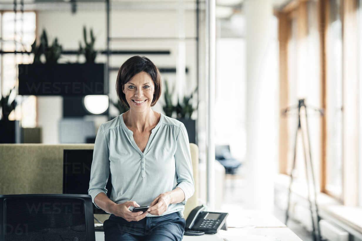 Glückliche Geschäftsfrau mit Smartphone im Büro - JOSEF03625 - Joseffson/Westend61