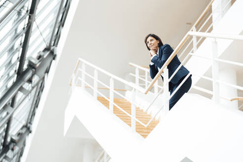 Thoughtful businesswoman with hand on chin leaning over railing in corridor - JOSEF03628