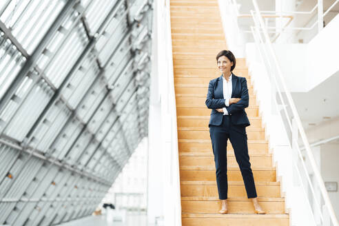 Smiling businesswoman with arms crossed standing on steps in corridor - JOSEF03634