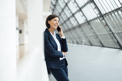 Businesswoman talking on smart phone while leaning on wall in corridor - JOSEF03643