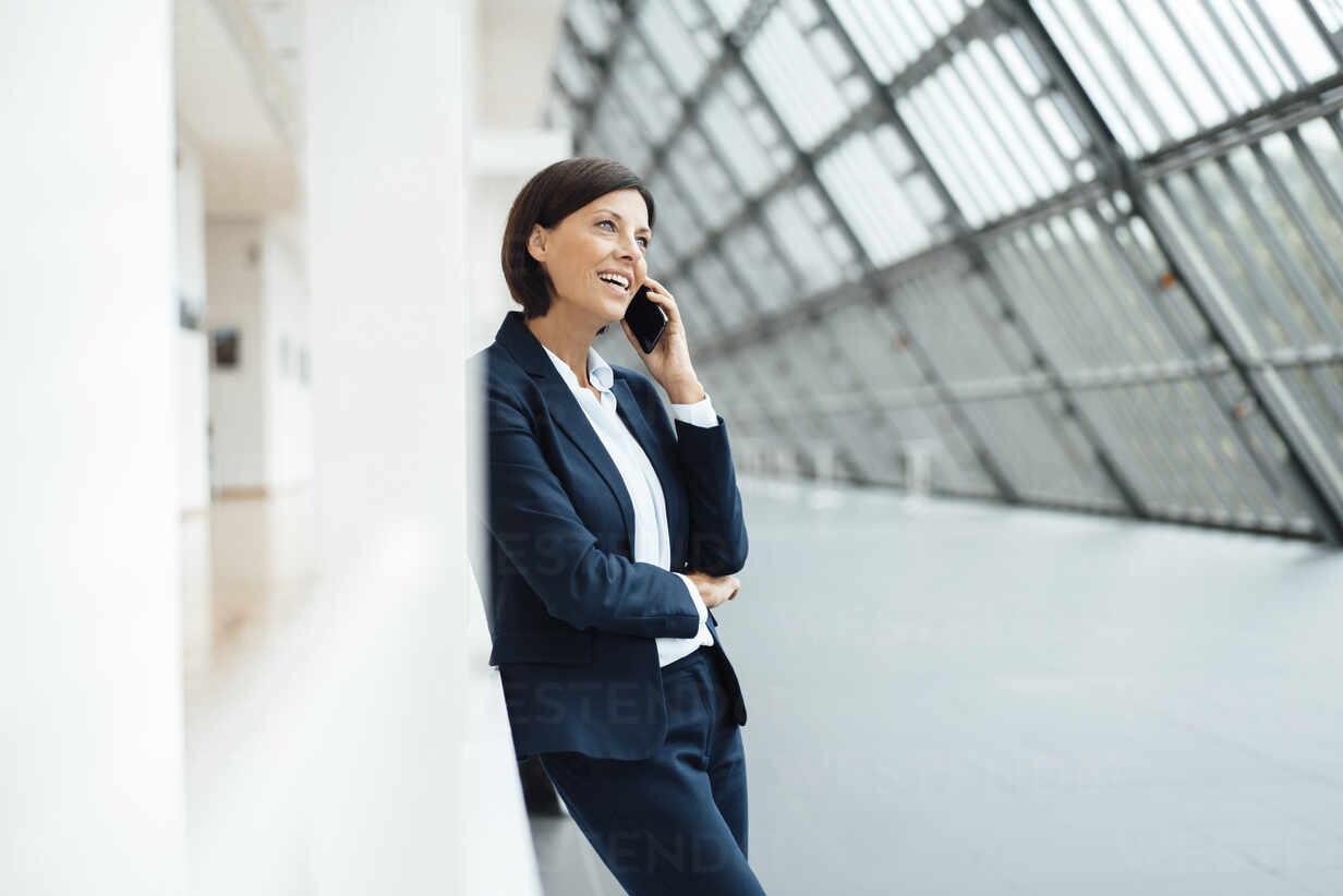 Businesswoman talking on smart phone while leaning on wall in corridor - JOSEF03643 - Joseffson/Westend61