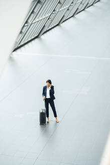 Businesswoman with suitcase talking on smart phone while standing at corridor - JOSEF03646